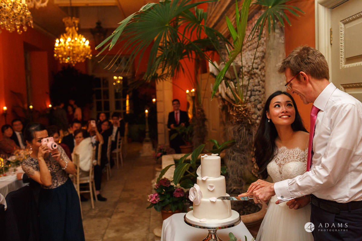 the lost orangery wedding photographer the married couple cut the cake