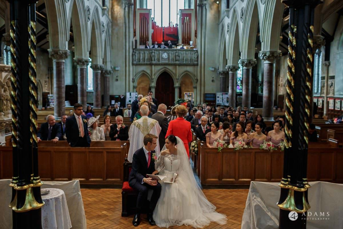 the lost orangery wedding the couple sits next to each other with the view of the church