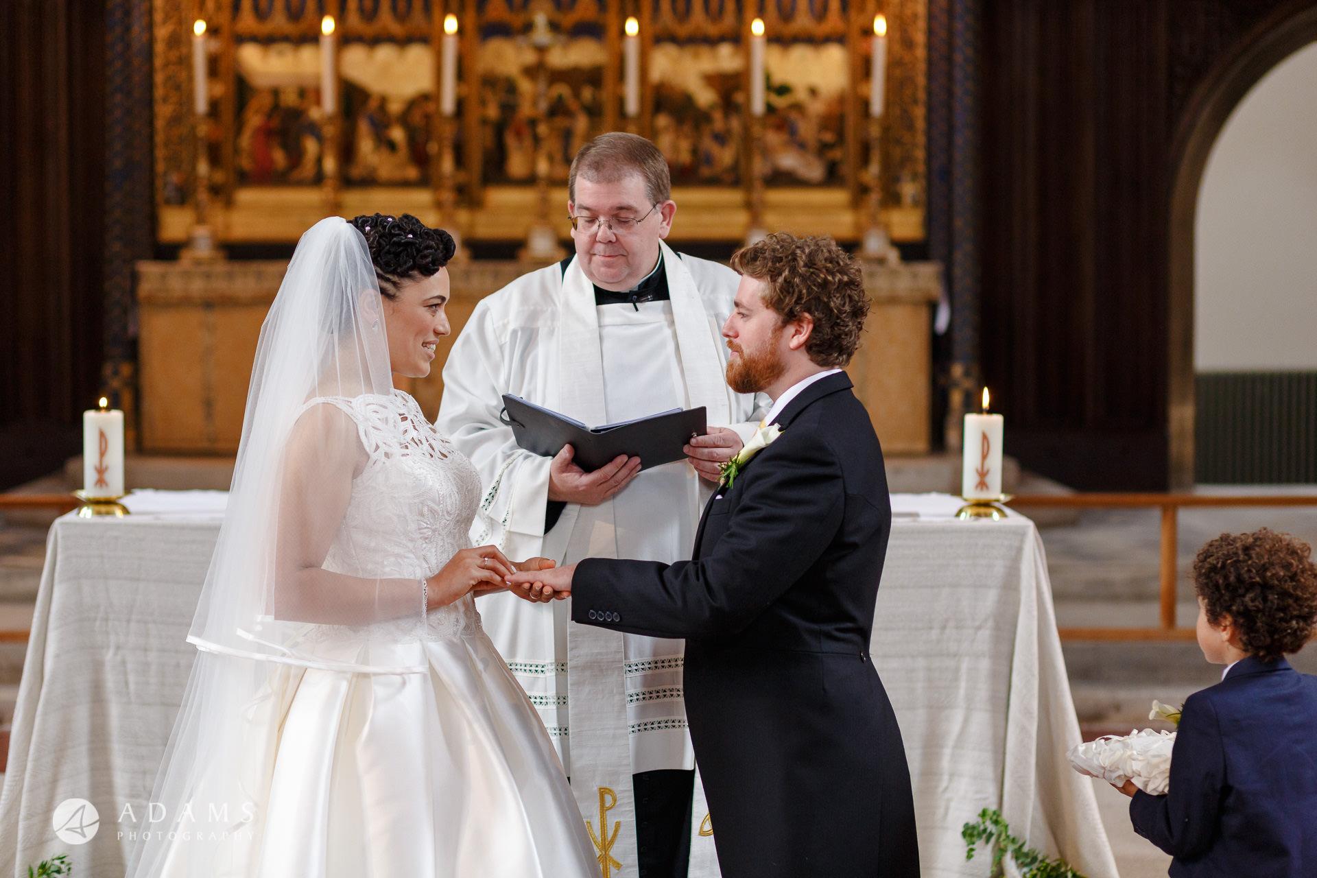 Morden Hall Wedding bride puts a ring on groom