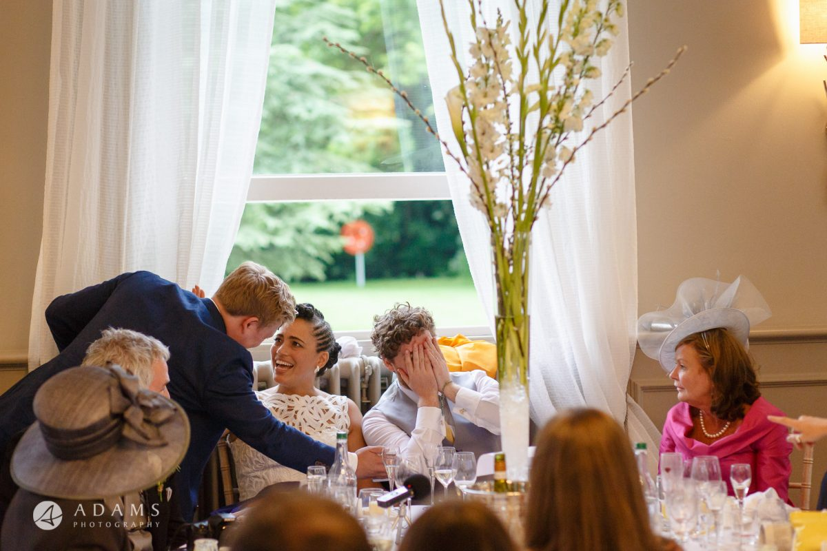 Morden Hall Wedding photographer groom covers his face in hands reaction