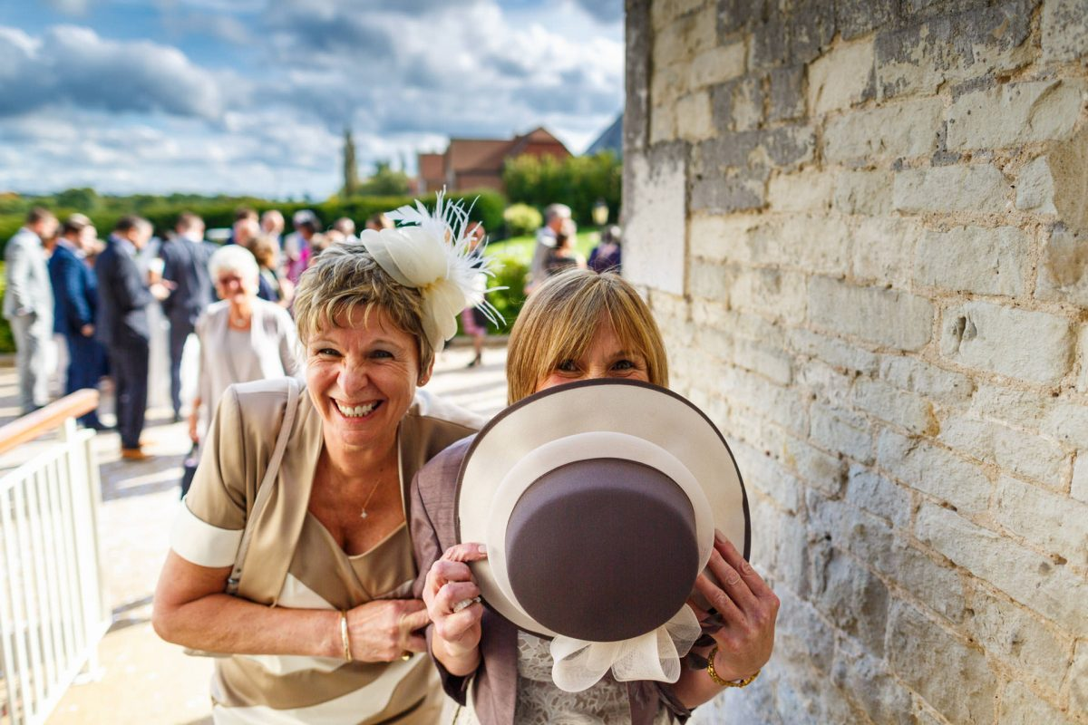 London Wedding Photography Portfolio guests hiding behind the hat
