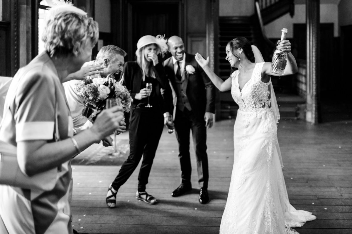 London Wedding Photography Portfolio bride opens a champagne