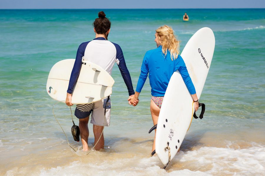 destination wedding photographer couple is walking with the surf boards