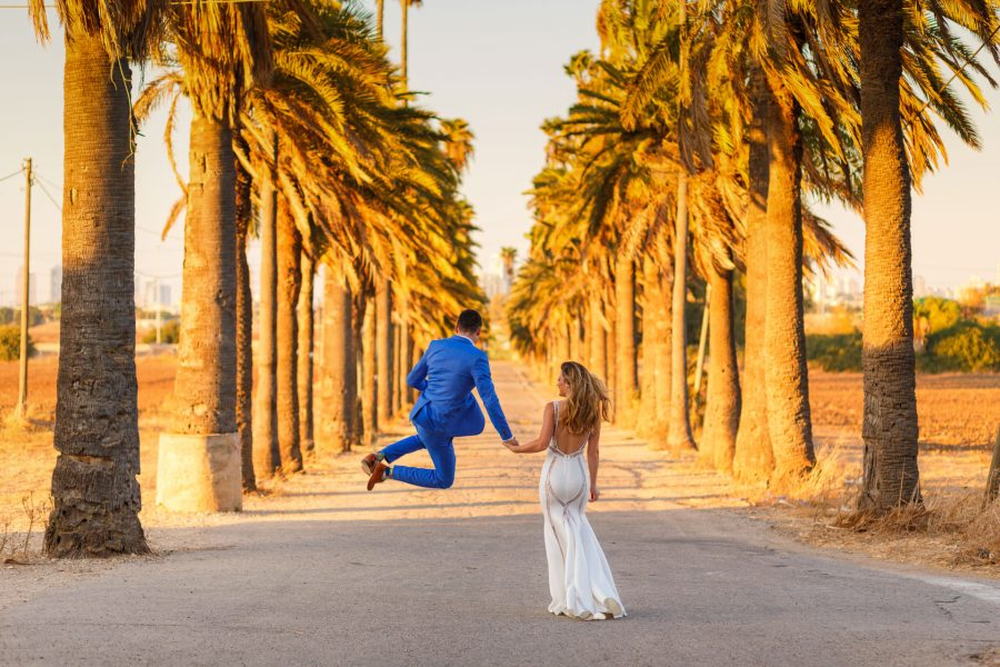 destination wedding photographer couple walks and jumps among the palms