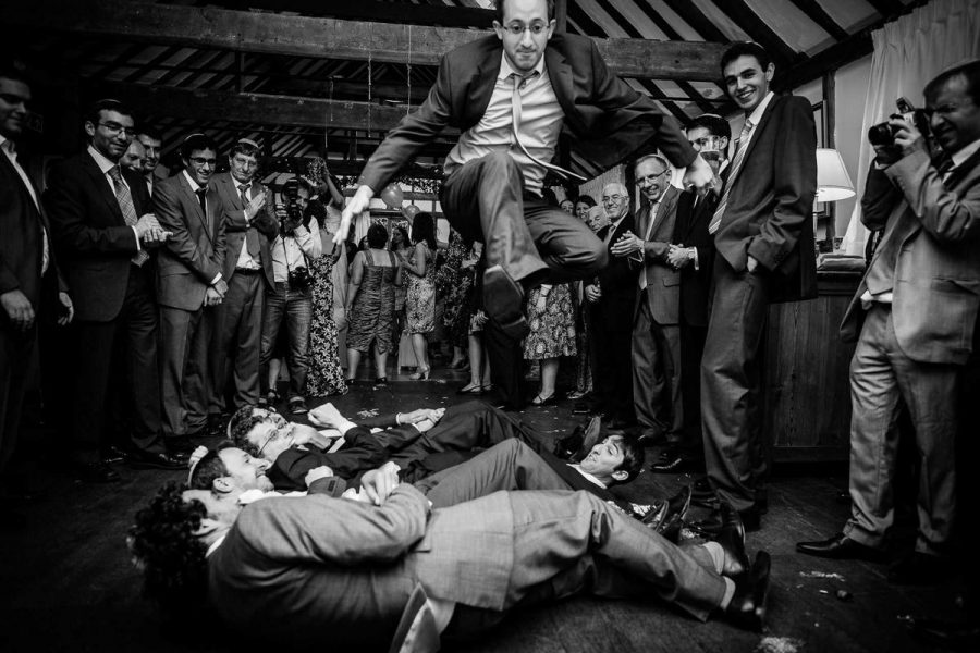 jewish wedding photographer groom is jumping over the freinds