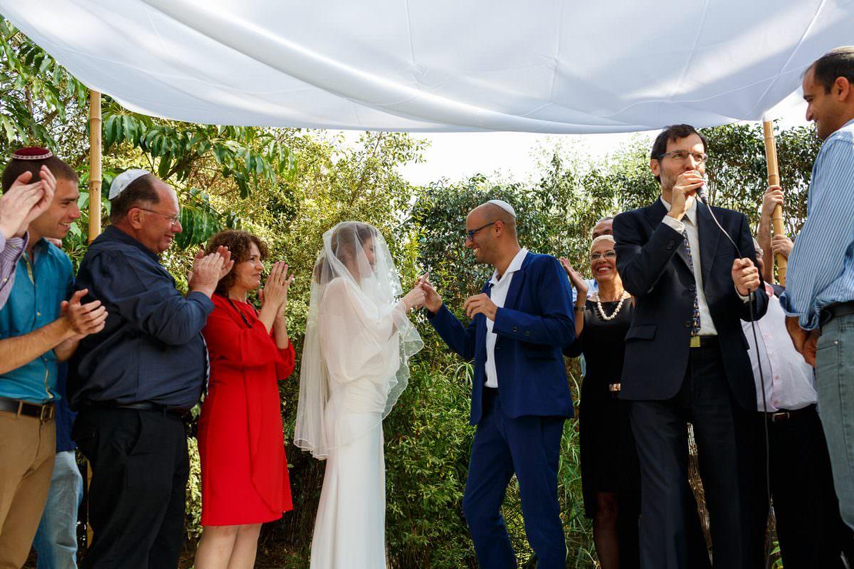 jewish wedding photographer groom put the ring on the bride