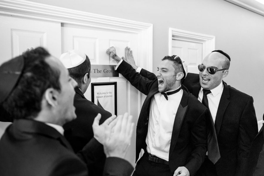 jewish wedding photographer groomsmen knock on the door