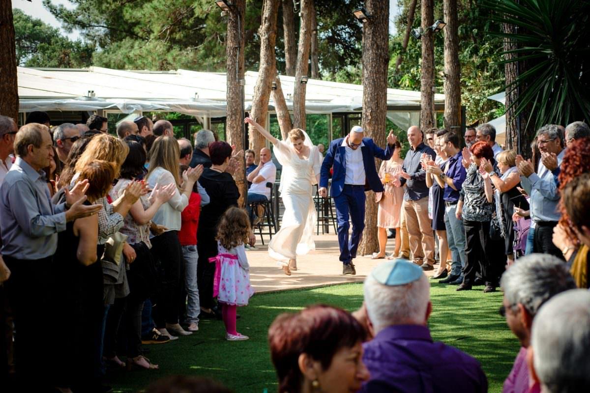 jewish wedding photographer couple jumps towards chupah
