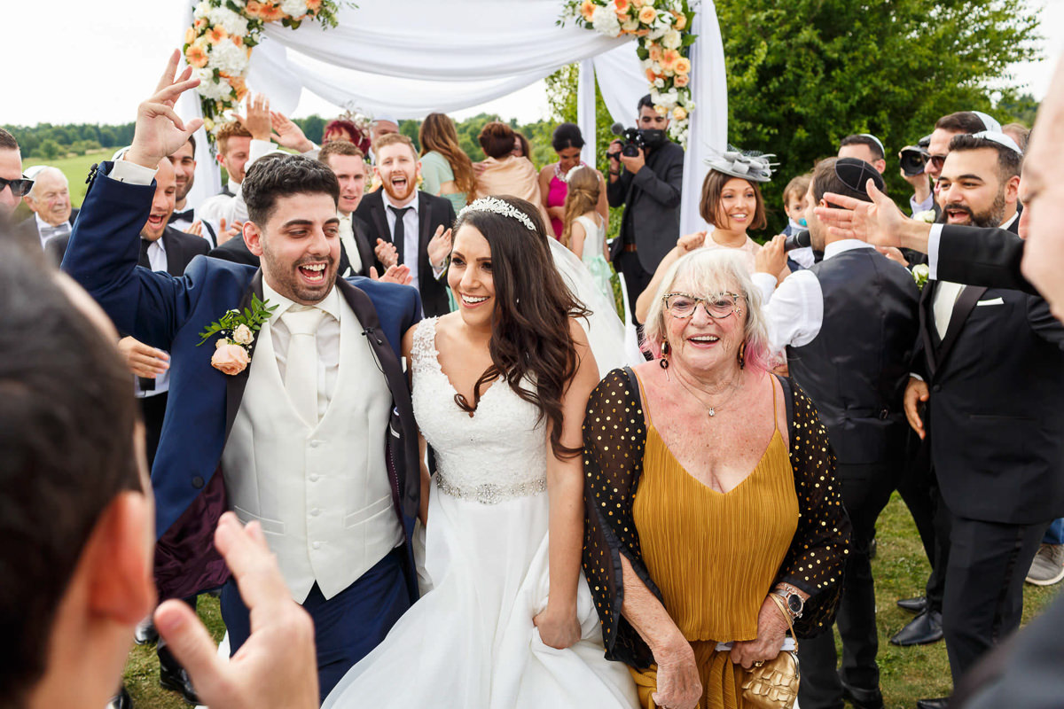 jewish wedding photographer couple just got married and walk out from the chuppah