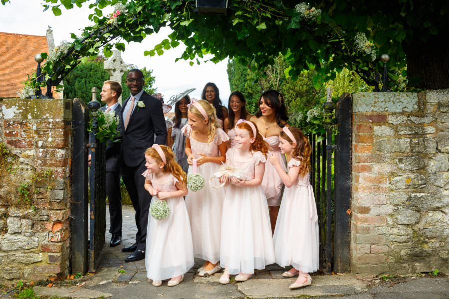Wedding photographers London flower-girls and bridal-party waiting for the bride in front of the church