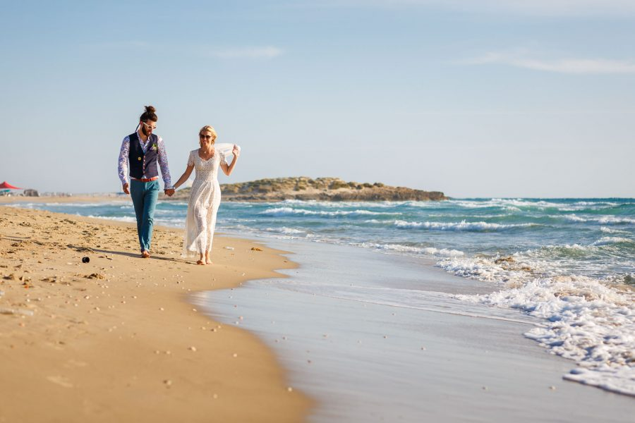 destination wedding photographer married couple walking by the sea