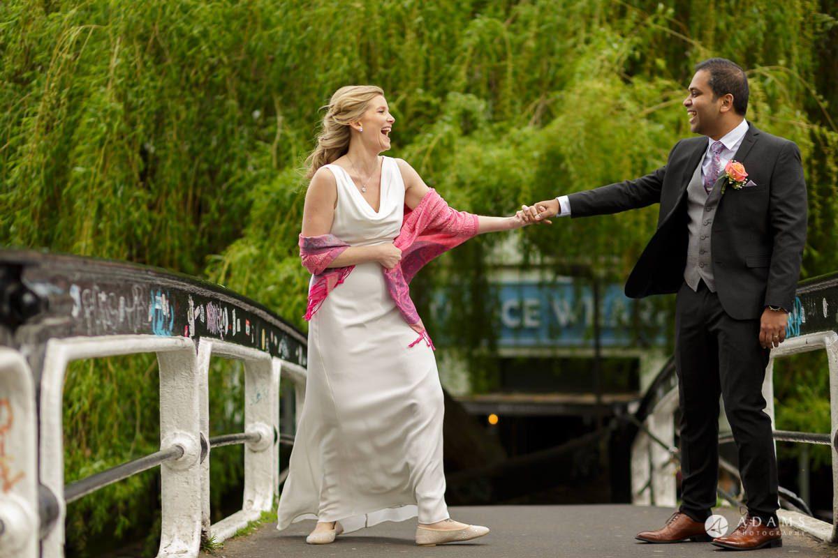 Camden Town wedding couple holding hands on the bridge