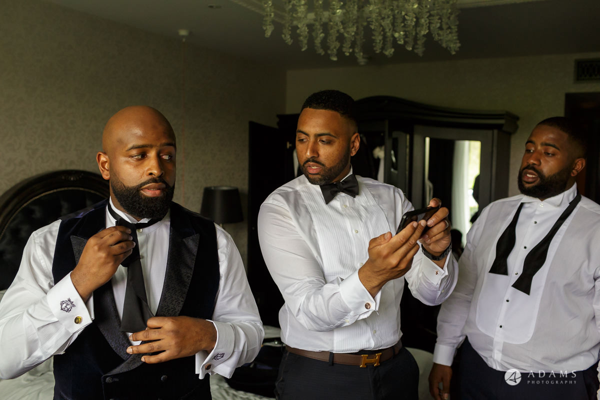 syon park house wedding photographer is learning how to tie a bow tie