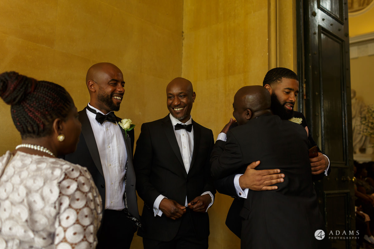 photographer syon park house wedding guests are hugging