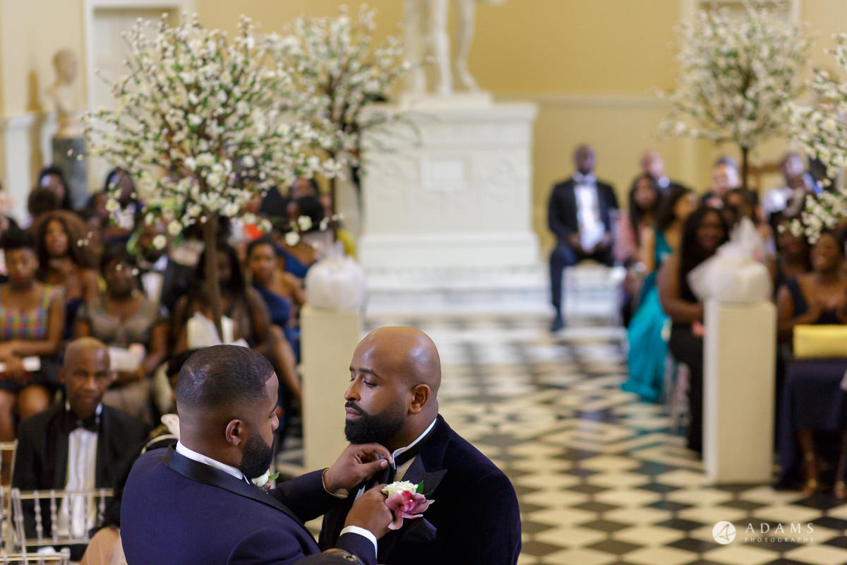 syon park house wedding groom has his tie fixed