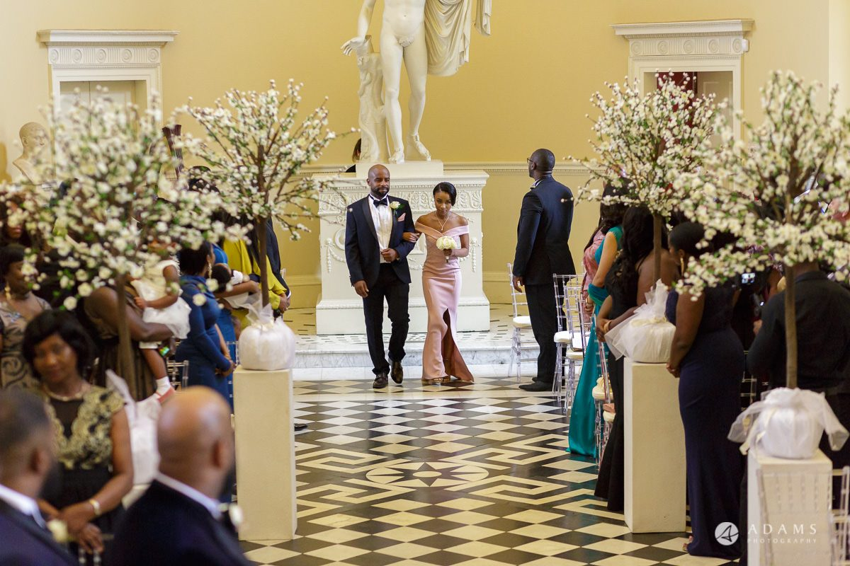 photographer syon park house wedding groomsman and bridesmaids walk down the aisle
