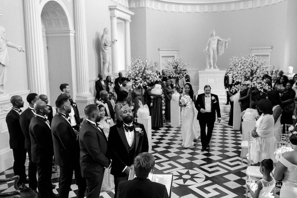 syon park house wedding groom is having an emotional moment while the bride is walking down the aisle wth her father