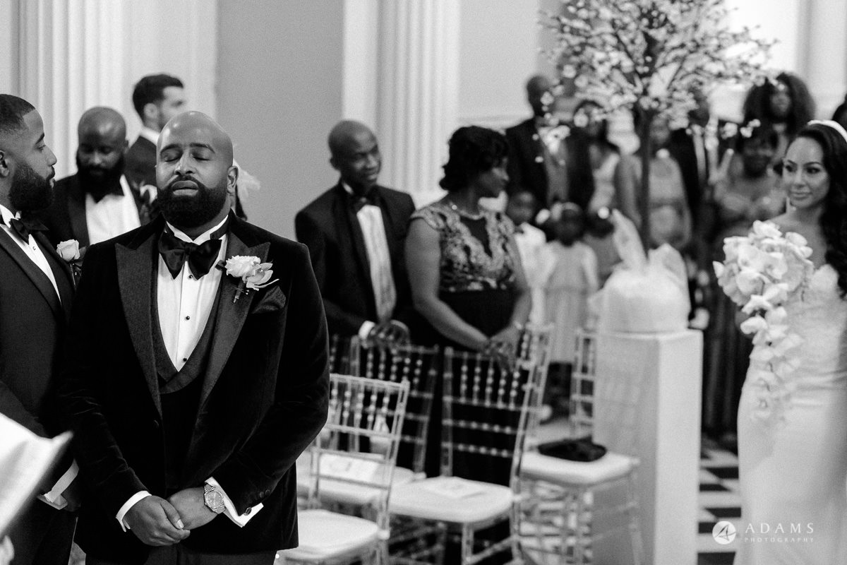 syon park house wedding photographer groom with his eyes closed