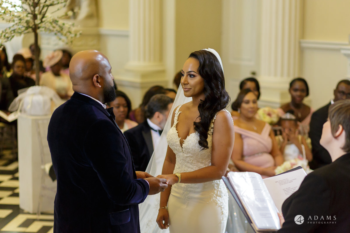 syon park house wedding photographer bride and groom exchange the rings