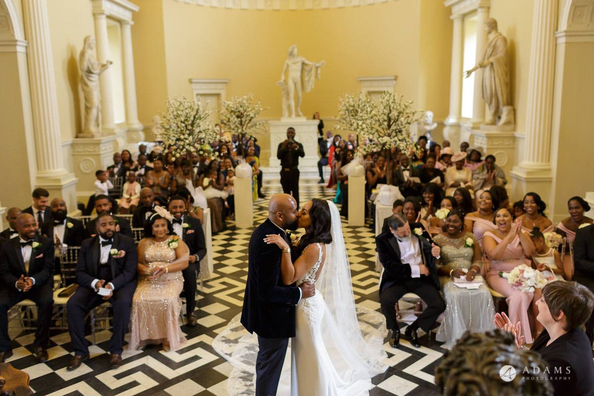 syon park house wedding bride and groom are having their first kiss