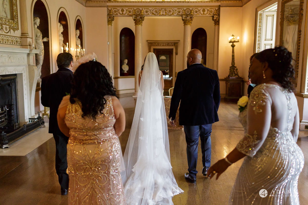 syon park house wedding bride and groom walk to sign the registrar