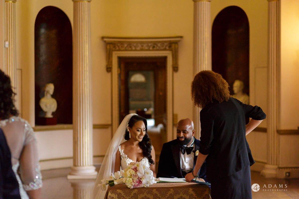 syon park house wedding the couple are siting and checking out the marriage certificate