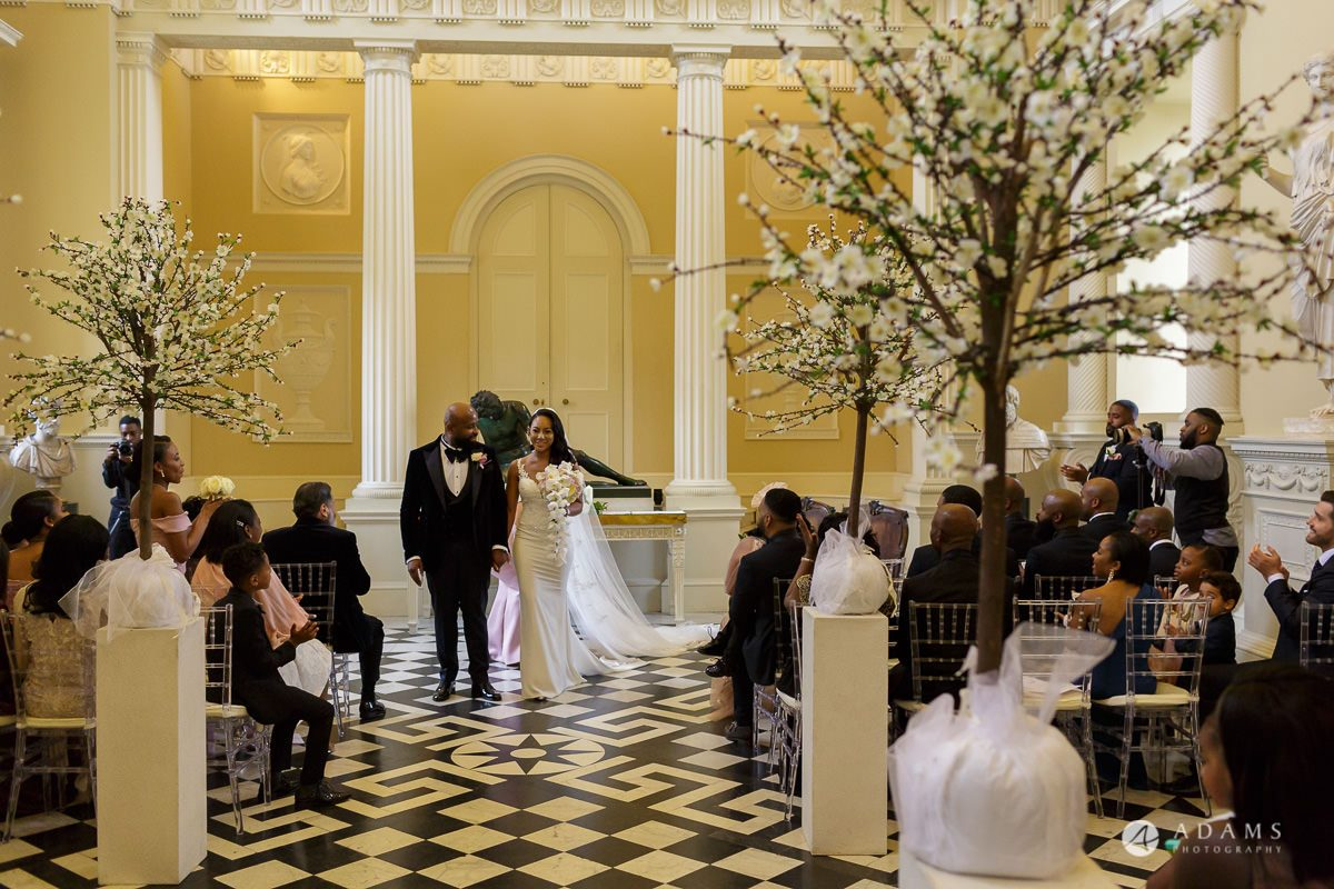 syon park house wedding bride and groom walks out the venue