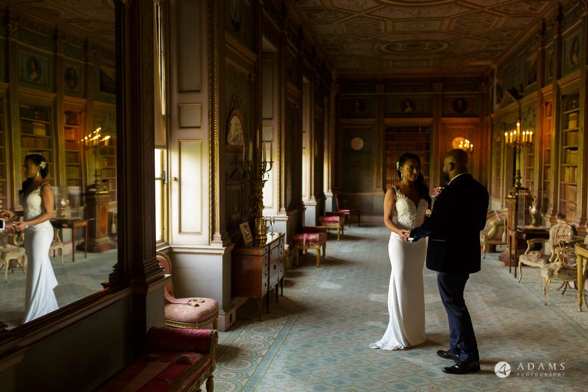 syon park house wedding couple holding hands in the walking room