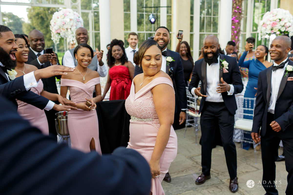 syon park house wedding bridesmaid dancing while entering the room