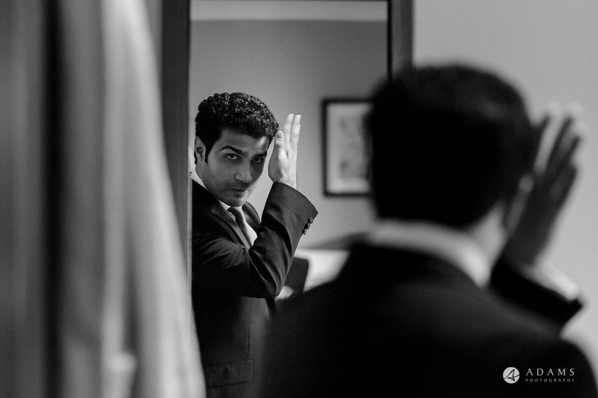 pinewood studios wedding groom fixing his hair by the mirror