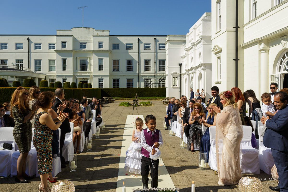 pinewood studios wedding page boy and a flower girl walking down the aisle