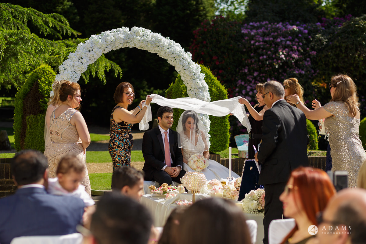 pinewood studios wedding family holds a cloth over the married couple