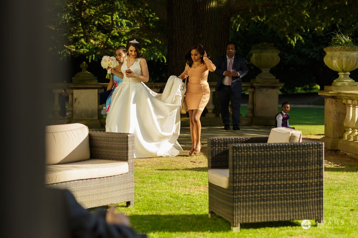 pinewood studios wedding bride walks whit the bridesmaids holding the wedding dress