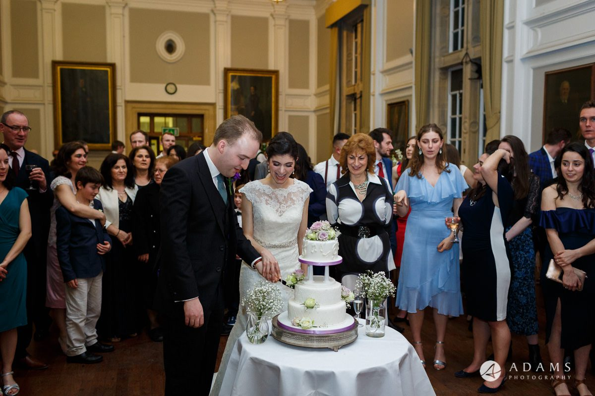 royal holloway wedding photography of cuting the cake