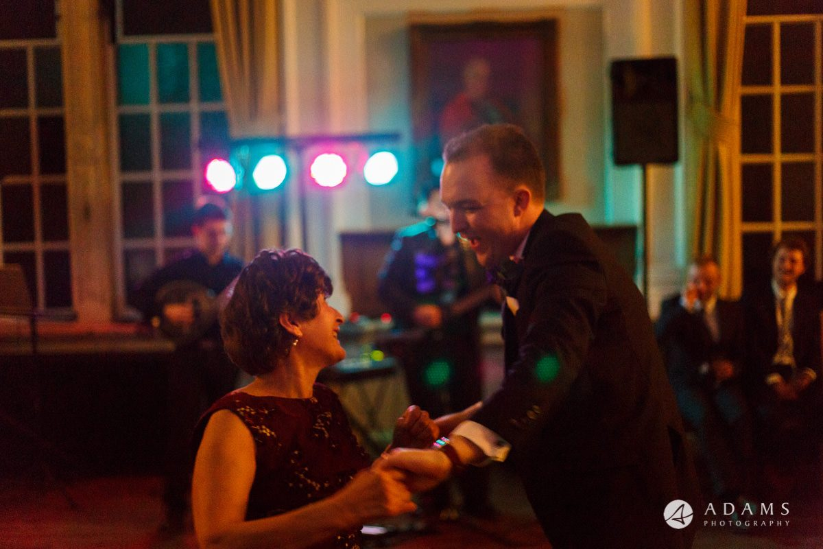 Royal Holloway wedding photographer groom dance with mother of the bride