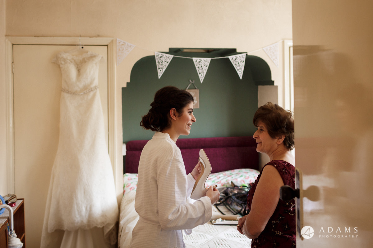 Royal Holloway Wedding bride shows shoes to her mou