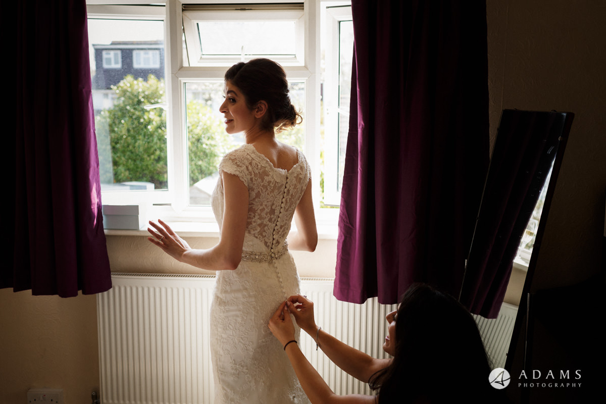 Royal Holloway Wedding bride putting on her dress