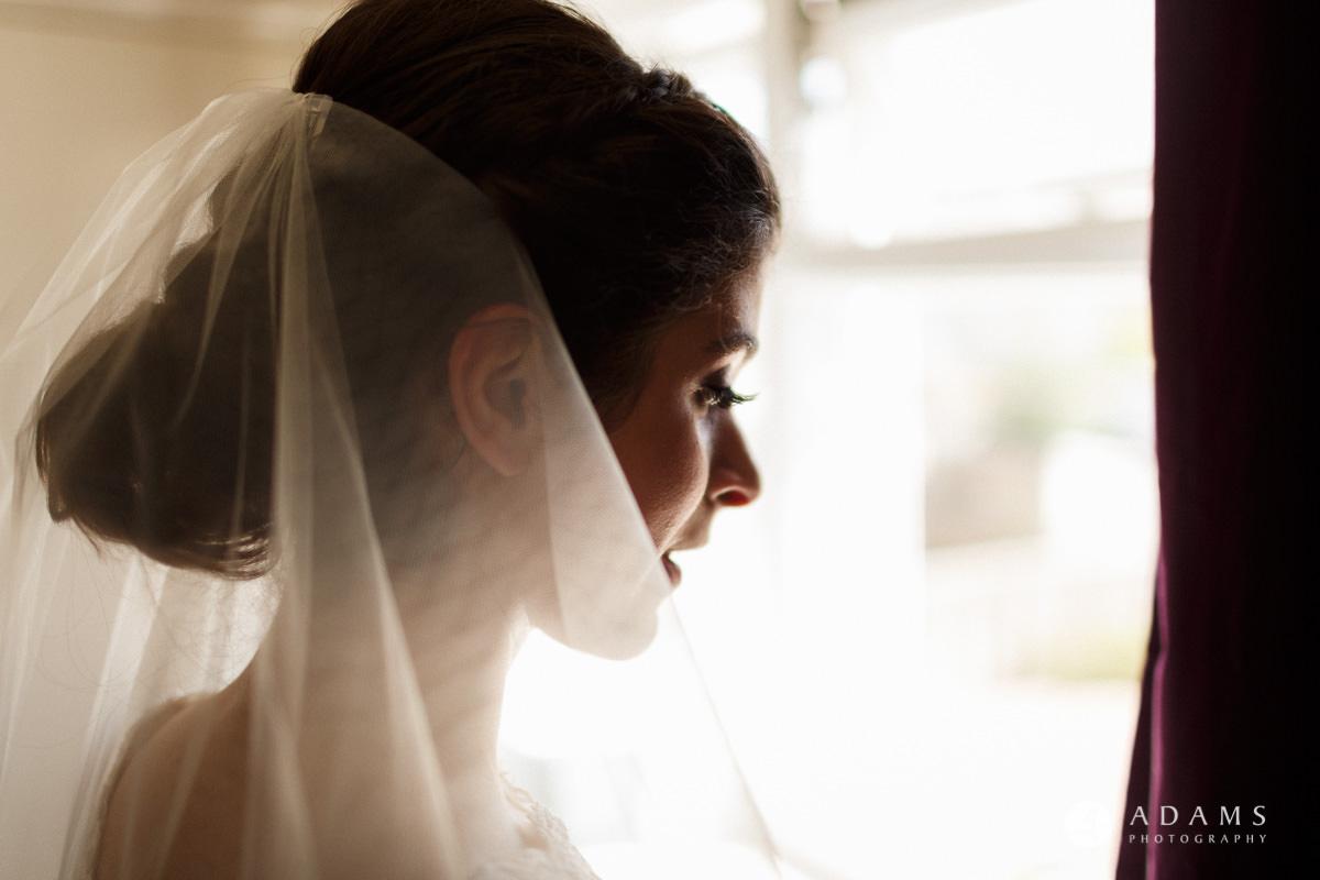 Royal Holloway Wedding bride looks through the window