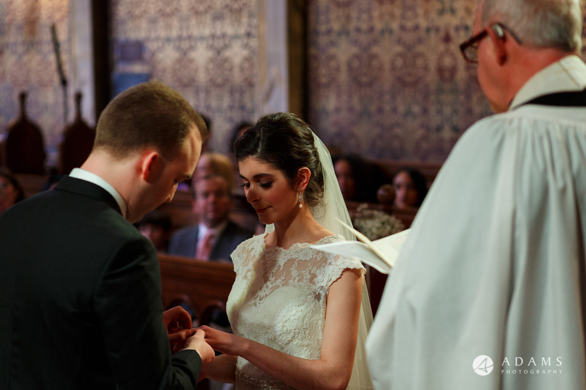 Royal Holloway wedding groom puts a ring on brides finger in the chapel