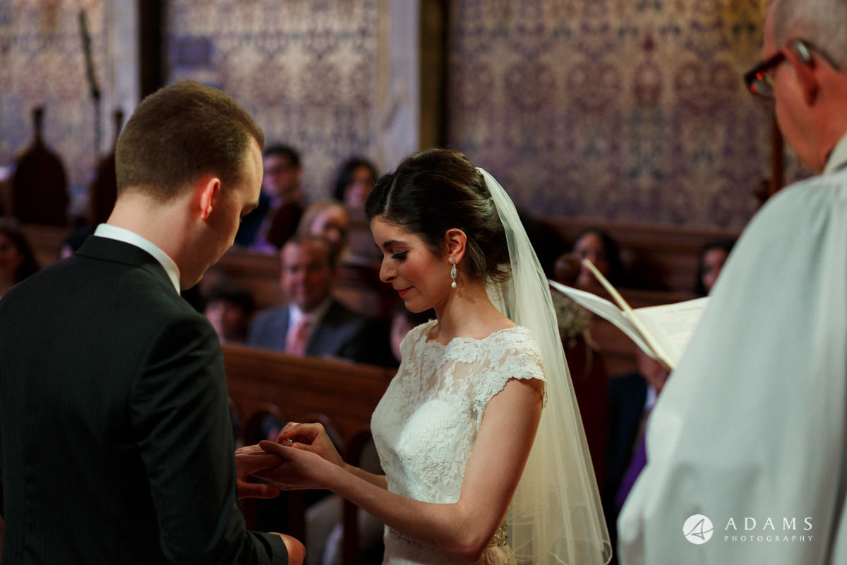 Royal Holloway wedding bride puts the wedding ring on grooms finger