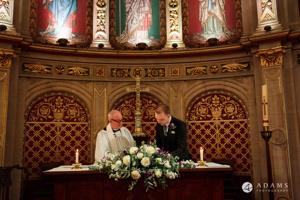 royal holloway wedding groom sining the registrar