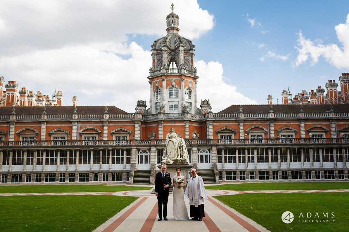 Royal Holloway wedding photo with the priest in the courtyard