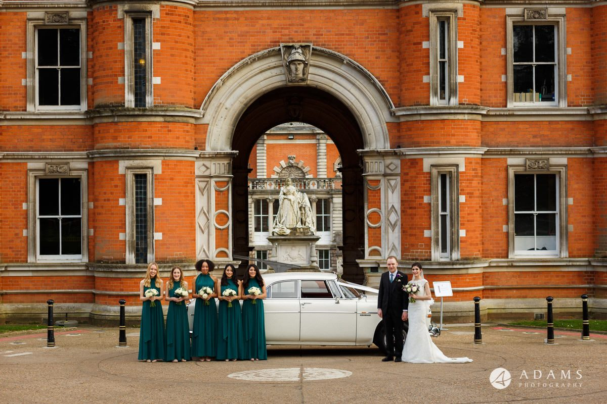 royal holloway wedding photographer bride groom and the bridesmaids posing by the car in front of the university entrance
