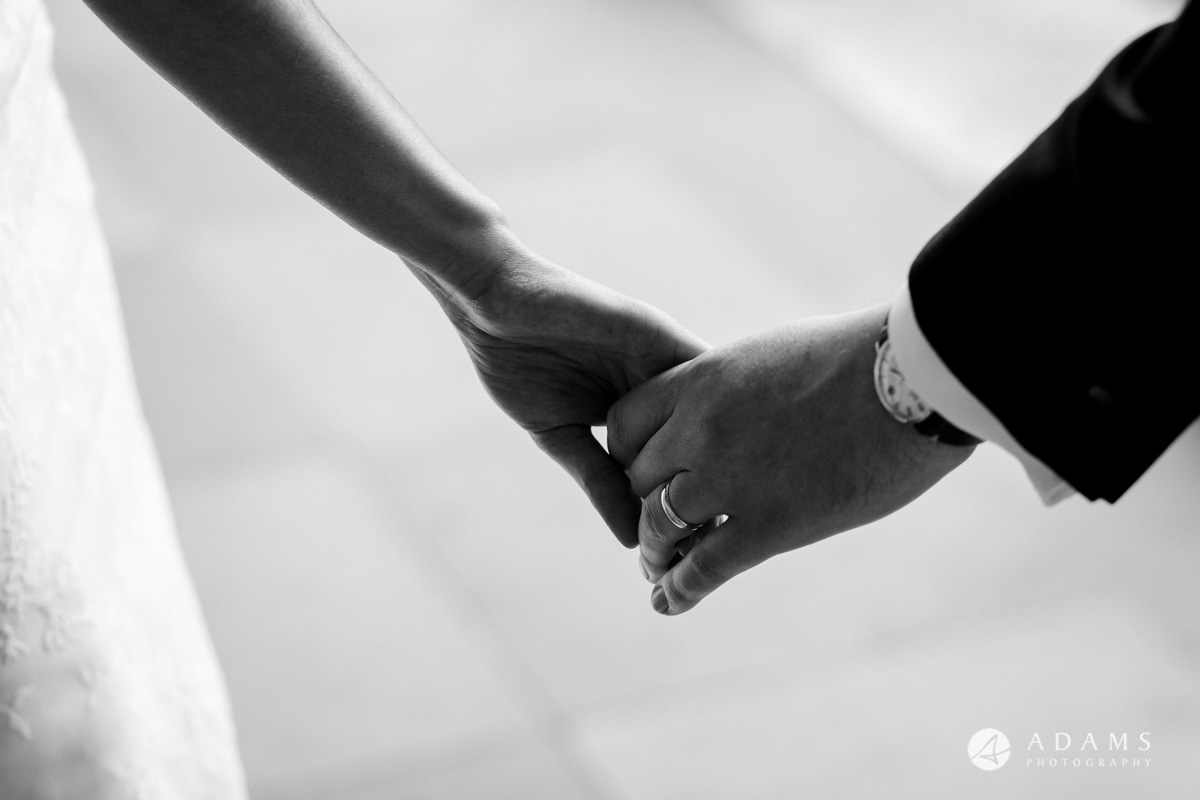 royal holloway wedding close up on the hands of bride and groom black and white photo