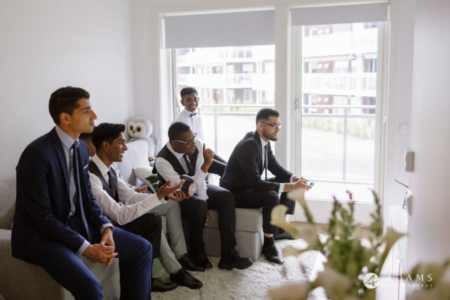 Oslo Wedding Photos Norway groom and groomsmen having good time playing football on TV