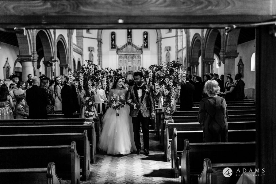 st donats castle wedding grooms and bride walk out of the church