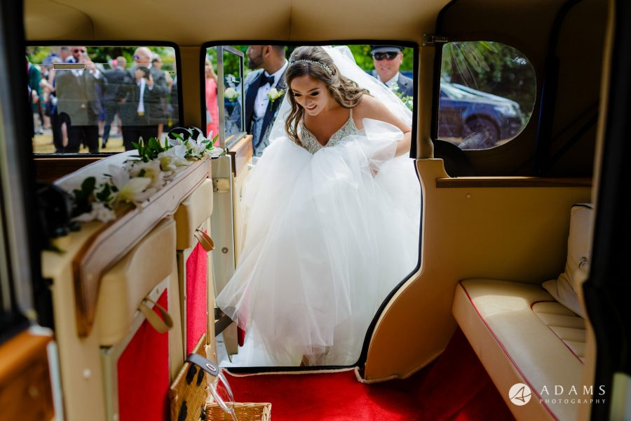 st donats castle wedding bride in her wedding dress is getting into the car