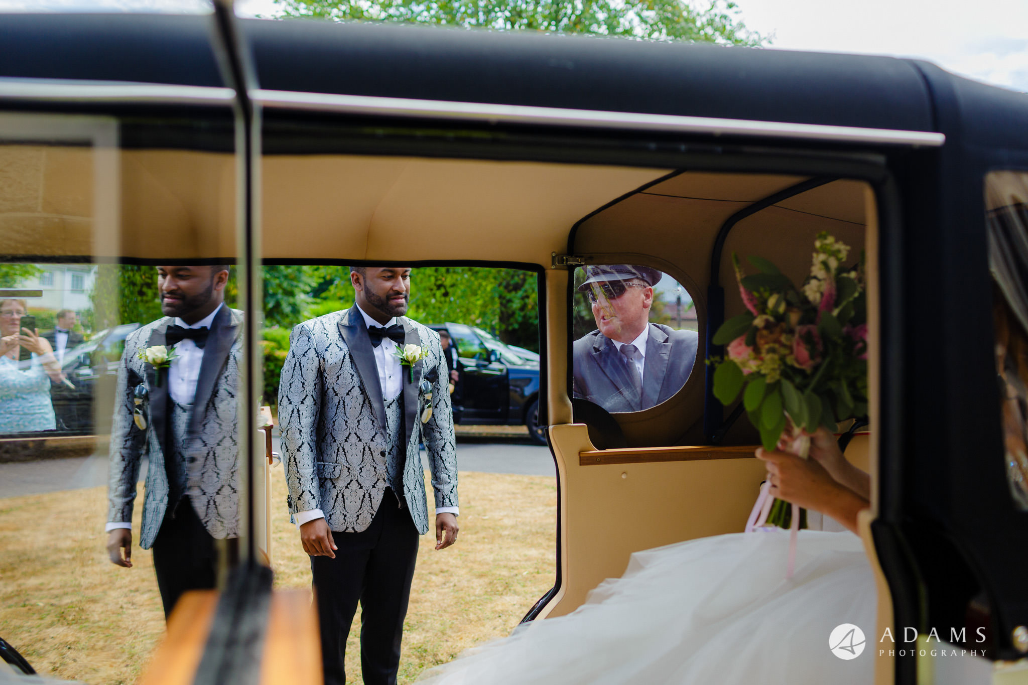 st donats castle wedding groom stands outside the car