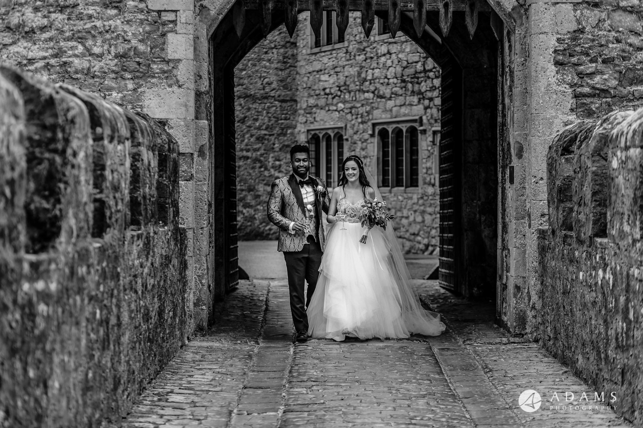 st donats castle wedding the married couple walk in from of the castle entrance gate