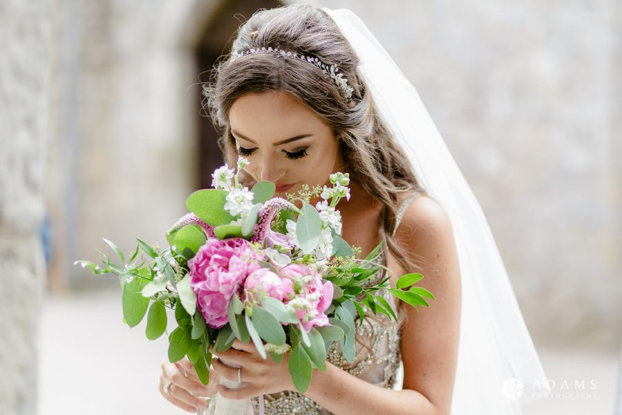 st donats castle wedding bride looking at her bouquet